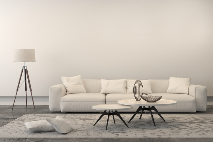White sofa with set of coffee tables, a floor lamp and pillows. Interior is white, brightly lit with ornate carpet. Concrete industrial floor and a white wall behing. Copy space. 3D render